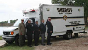 A group of men in suits stand in front of an Eddy County Sheriff's emergency vehicle
